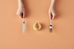 Fettuccine pasta, fork and knife in hands isolated on beige background, minimalistic photography for food blog or ad