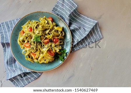 Fettuccine pasta with pesto sauce. Basil and pine nuts on concrete background. Italian cuisine. Top view. Copy space. Top view.  #1540627469
