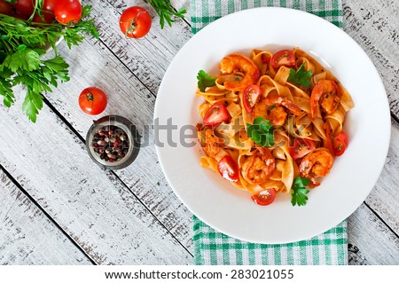 Fettuccine pasta with shrimp, tomatoes and herbs. Top view