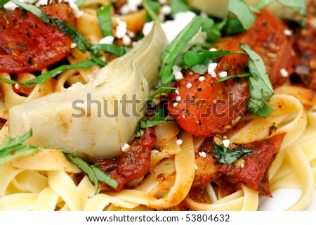 Fettuccine topped with tomatoes roasted in olive oil and italian herbs and spices with marinated artichoke hearts sliced fresh basil and feta cheese