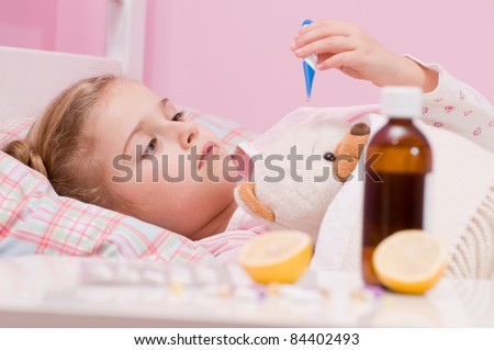 Fever, cold and flu - Medicines and hot tea in front, sick girl with teddy bear in bed ( No-name teddy bear )