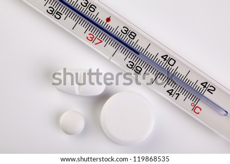 Fever thermometer showing a temperature of 39 degrees celsius and some pills