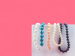 Few beads of mix color pearls hanging on a white box on pink background, copy space.
