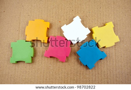 Few colorful empty puzzles on a cardboard background.