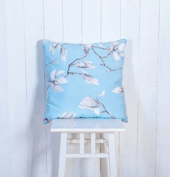 Few Colorful pillows on chair. Modern interior with chair and pillow on white wooden wall background