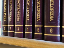 Few encyclopedia volumes, standing on a bookshelf, with close-up on golden volumes' numbers