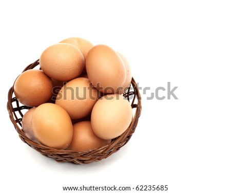 few fresh raw brown eggs in a basket over white