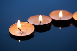 Few lighting candles on dark blue water surface