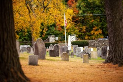 Few old gravestones are on the yellow grass among dry fall leaves on the ancient cemetery and red, yellow, orange, green trees along with a stone fence on the background on a sunny warm day
