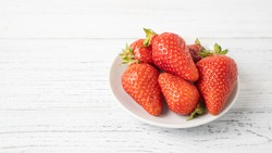 Few ripe strawberries on white small plate on wooden table Isolated strawberry bowl on white background Summer pleasure