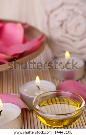 Few spa products with rose petals, oil container, towel and candles