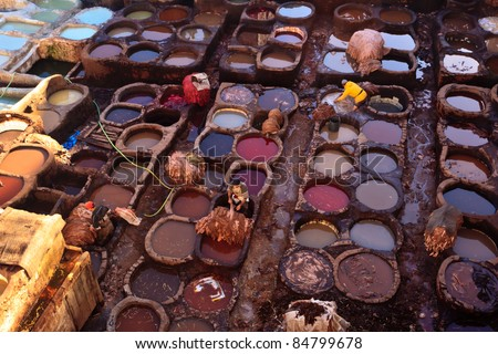 FEZ, MOROCCO - DEC 22: Unidentified laborers dye animal hides in colorful tanning vats at a traditional leather tannery,  December 22, 2009 Fez, Morocco.