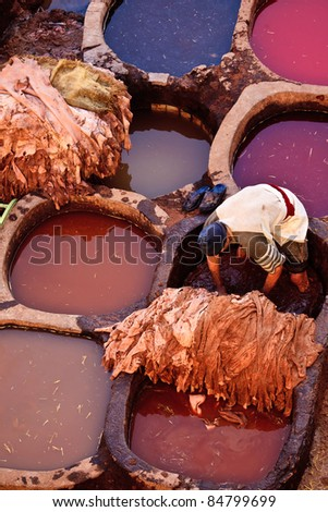 FEZ, MOROCCO - DEC 22: Unidentified man working in colorful tanning pools of traditional leather tannery, Dec. 22, 2009, Fez Morocco