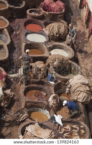 FEZ, MOROCCO - MAY 7: Local people painting leather at the tannery the ancient way with natural products like saffron, poppy,ceder and indigo at May 7,2013 in Fez, Morocco.