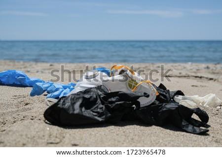 Ffp protective virus mask and plastic gloves garbage trash on sandy sea coast,coronavirus covid pollution disease