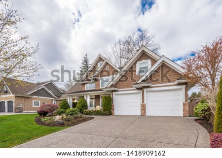 Fgrament of beautiful exterior of newly built luxury home. Yard with green grass and landscape. #1418909162