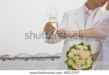 Fiance look to bride, holding glasses of champagne