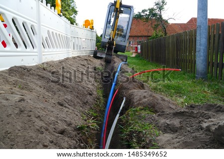 Fiber optic cable laying in the ground, buried cable for faster internet in rural region - 	underground cabling in Rodewald, district of Nienburg, Lower Saxony, Germany #1485349652