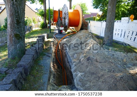 Fiber optic cable laying in the ground, buried cable for faster internet in rural region, near the village Eschede, district Celle, Lower Saxony, Germany