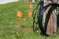 Fiber optic cable, orange marking flags and utility pole. Concept of digging safety, utility locate service and high speed internet.