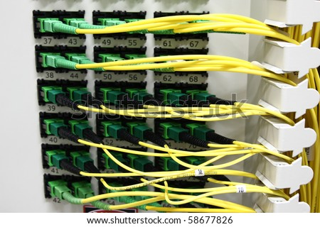 Fiber Optics with SC/APC connectors - Patch Panel. Internet Service Provider equipment. Focus on fiber optic cables. Data Network Hardware Concept.