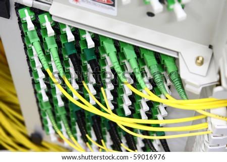 Fiber Optics with SC/APC connectors - Patch Panel. Internet Service Provider equipment. Focus on fiber optic cables. Data Network Hardware Concept.
