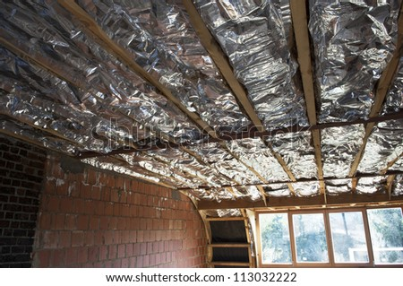 Fiberglass insulation installed in the sloping ceiling of a house.