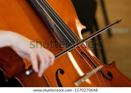 Fiddlestick on the strings of a cello closeup
