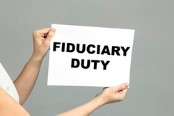 FIDUCIARY DUTY text is written on paper. Business woman holding a sheet with FIDUCIARY DUTY an inscription on a white background. Business concept.