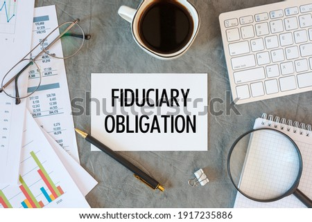 Fiduciary Obligation is written in a document on the office desk with office accessories, diagram and keyboard Stock foto ©
