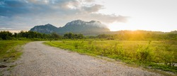 Field and dirt road to sunset behind mountain