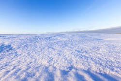 field, covered with pure snow in the winter season in the background a blue sky
