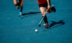 Field hockey player, in possesion of the ball, running over an astroturf pitch, looking for a team mate to pass to. Blue color filter