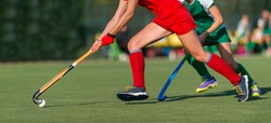 Field Hockey player, ready to pass the ball to a team mate. Hockey is a team sport.