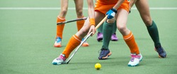 Field hockey players challenge eachother for possession of the ball on the midfield battle of a hockey mach