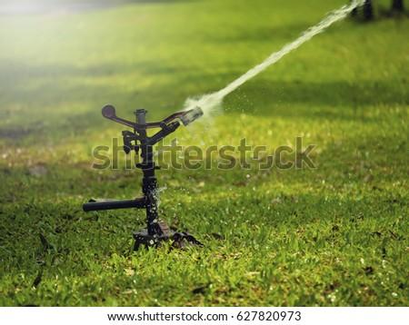 field hosepipe sprinkler grass water #627820973