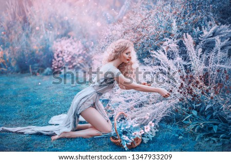 Photo of  field mermaid collects herbs and flowers in small basket. slender forest nymph sits on her knees in long light dress with open bare legs and back, glare of bright sun in magical purple and blue glade