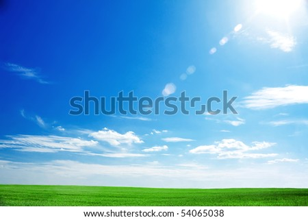 field of fresh green grass and bright blue sky with the sun causing lens flare