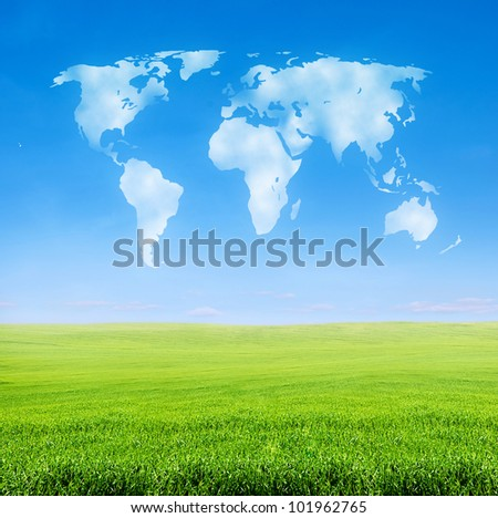 field of green grass over blue sky with world shaped clouds