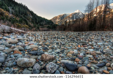 Field of natural stones with mountains and forest in background