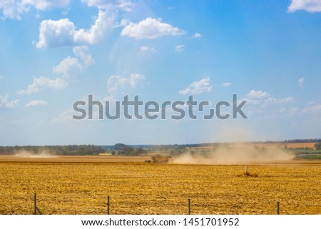 field of yellow grass and combines harvesting wheat