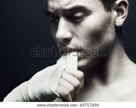 Fierce athlete with a bandage in his mouth