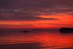 fiery red sunset on the sea, red volumetric sky and red water, beautiful red evening landscape