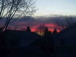 Fiery sunrise over the neighborhood houses coloring the sky fiery red