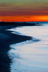 Fiery sunset along a Lake Michigan shoreline.