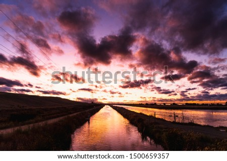 Fiery sunset in South San Francisco bay area with bright sunlight reflected on the water surface of a creek; Sunnyvale, California ストックフォト ©
