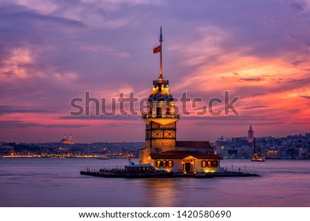 Fiery sunset over Bosphorus with famous Maiden's Tower (Kiz Kulesi) also known as Leander's Tower, symbol of Istanbul, Turkey. Scenic travel background for wallpaper or guide book
