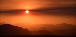 fiery sunset over the front range of the colorado mountains due to the smoke from  the western forest fires, as seen from broomfield, colorado
