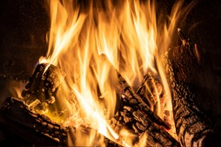Fiery yellow orange tongues on dark background rise up in a brick fireplace burning flame, fire close-up photo