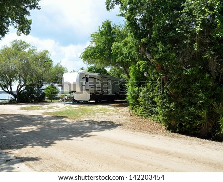 Fifth wheel camper parked at a  camping site along the river's edge at Florida.